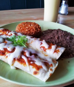 Breakfast Enchiladas with ground beef patties and a side of re-fried beans and Spanish rice :) DROOL